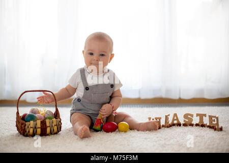 Süße kleine Kleinkind Kind, baby boy, im sonnigen Wohnzimmer spielen mit Ostern Schokoladenhasen und bunte Ostereier - Stockfoto
