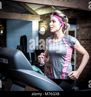 Mädchen auf einem Laufband trainieren im Fitnessraum, - Stockfoto
