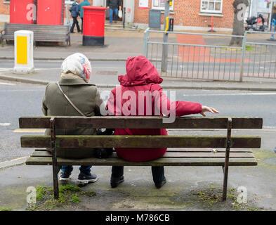 Wetter, Bridport, England, UK Freitag, den 9. März 2018. Zwei Frauen sitzen auf einer Bank in Bridport High Street - Stockfoto