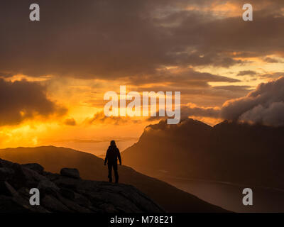 Eine Person in Silhouette einen Sonnenuntergang am Kjerringøy in Nordnorwegen.