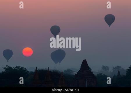 Heißluftballons über Tempel bei Sonnenaufgang an der gemauerten Damm in der Nähe von Taungbi Dorf in Bagan, Myanmar - Stockfoto