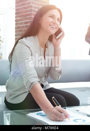 Frau Assistant auf einem Smartphone und Notizen in einem Tagebuch. Foto mit kopieren. - Stockfoto