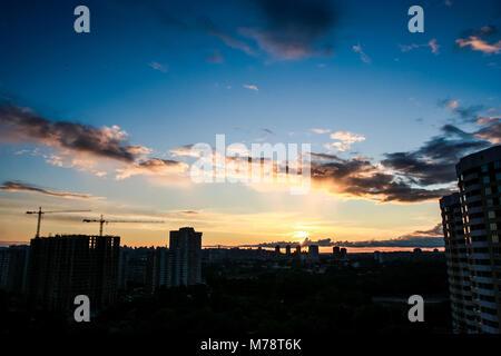 Der strahlend blaue Himmel mit weißen und rosa Wolken bei Sonnenuntergang über dunklen Silhouetten der großen Stadt - Stockfoto