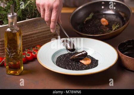 Küchenchef Meeresfrüchte, Muscheln, Garnelen nach Pinzette Essen in eine weiße Platte - Stockfoto