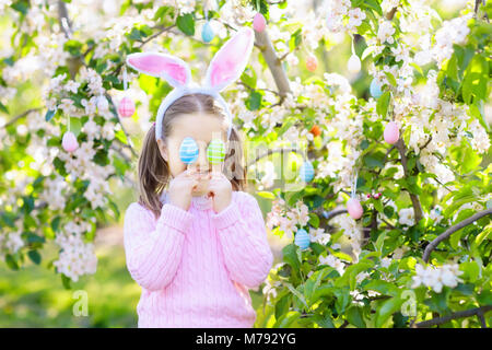 Kind auf Ostereiersuche im blühenden Kirschbaum Garten mit Blumen. Kind mit farbigen Eier im Korb. Kleines Mädchen - Stockfoto