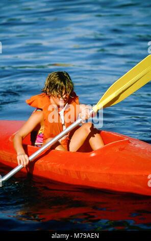 Ein 10-jähriges Mädchen lernt, wie ein Kajak im Summer Camp in Vermont, USA, Nordamerika zu paddeln. - Stockfoto