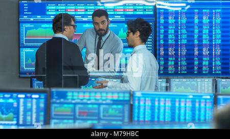 Drei erfahrene Lager Händler sprechen. Sie arbeiten für eine große Börse fest. Büro ist voll von Anzeigen für Daten, - Stockfoto