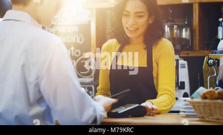 Im Café schöne Hispanic Frau macht Kaffee zum Mitnehmen für einen Kunden, zahlt sich durch berührungslose Handy - Stockfoto