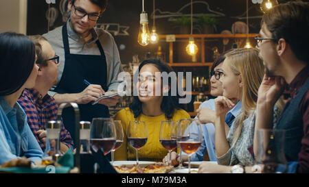 In der Bar/Restaurant Kellner nimmt um eine vielfältige Gruppe von Freunden. Schöne Menschen Wein trinken und eine - Stockfoto