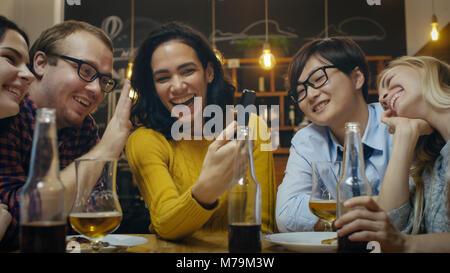 In der Bar/Restaurant Hispanic Frau macht Video Gespräch mit Ihren Freunden. Gruppe Schöne junge Menschen in der - Stockfoto