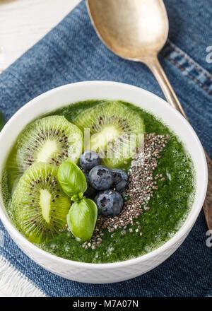 Gesunden grünen Smoothie Spinat, Banane, Avocado, Kiwi mit Chia Samen und Heidelbeeren. Detox. Gesundes Frühstück. - Stockfoto