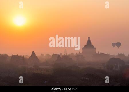 Sonnenaufgang und Heißluftballons über Tempeln in Backstein Damm in der Nähe von Taungbi Dorf in Bagan, Myanmar - Stockfoto