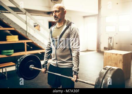 Passen reifer Mann in Sportkleidung alleine stehen in einem Fitnessstudio Gewichte während einer Trainingseinheit - Stockfoto