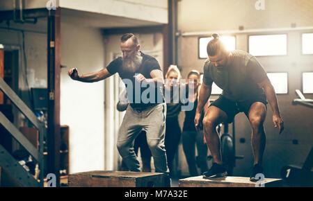 Zwei passen mir tut, springt während einer Übung Klasse in einer Turnhalle mit Freunden beobachten im Hintergrund - Stockfoto