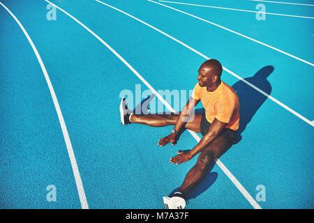 Schwerpunkt junge afrikanische männlichen Athleten in Sportkleidung alleine sitzen auf den Fahrspuren einer Laufstrecke - Stockfoto