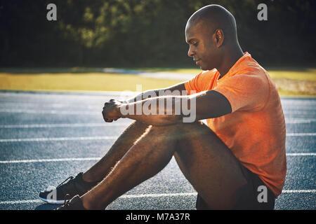 Schwerpunkt junge afrikanische männlichen Athleten in Sportkleidung alleine sitzen auf einem Runnng Titel mentale - Stockfoto