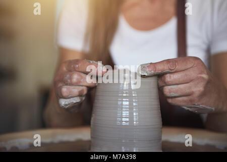 Kreative handwerkliche Gestaltung nassen Ton mit den Händen auf einer Töpferei Rad beim Sitzen in Ihrem keramische - Stockfoto