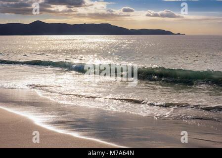 Brechenden Wellen bei Spirituosen Bay (Piwhane) mit Cape Reinga im Abstand, North Island, Neuseeland - Stockfoto