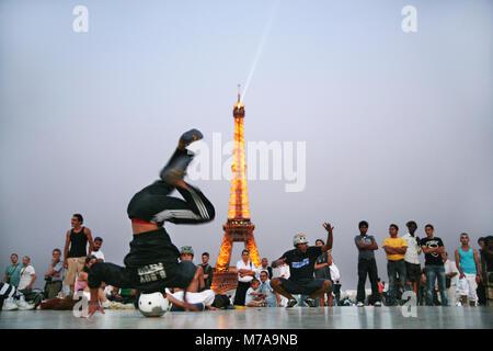 Breakdancer, eine Menge von Touristen in der Nähe von Eiffelturm unterhalten wie abends mit den Städten Lichter - Stockfoto