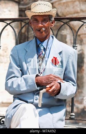 Porträt von einem älteren Mann sitzt auf einem Felsvorsprung und Zigarre - Stockfoto
