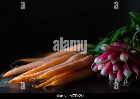 Ein paar Radieschen und eine frische Karotte Bündel auf einer Tabelle mit einem schwarzen Hintergrund in natürlichem - Stockfoto