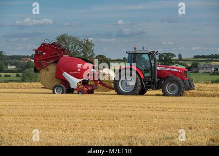 Pressen von Stroh in Bauernhof Feld, Landwirt arbeitet und Laufwerke, Red Tractor Pulling Rundballenpresse (nur - Stockfoto