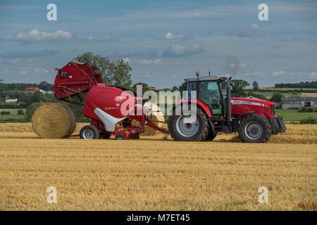 Pressen von Stroh in Bauernhof Feld, Landwirt arbeitet und Laufwerke, Red Tractor Pulling Rundballenpresse (große - Stockfoto