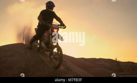 Professionelle Motocross Motorradfahrer fährt auf der Düne und stoppt auf der Oberseite. Es ist Sonnenuntergang - Stockfoto