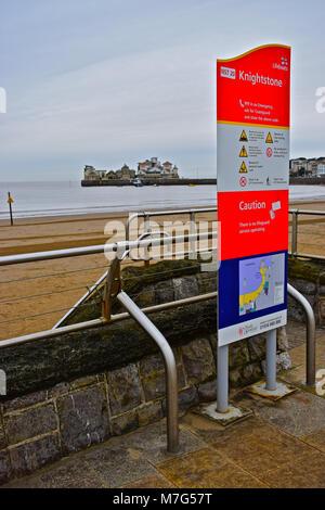 Warnschild einen Blick auf den Strand von Weston-super-Mare mit dem historischen Knightstone Insel im Hintergrund. - Stockfoto