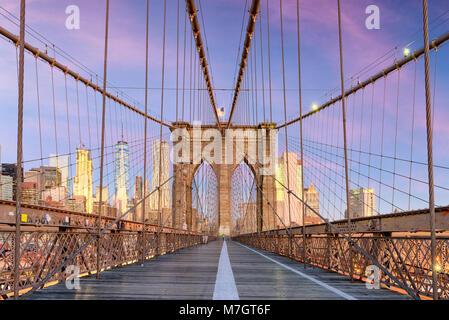 New York, New York auf der Brooklyn Bridge, Promenade mit Blick auf die Skyline von Manhattan in der Morgendämmerung. Stockfoto