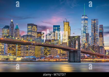 New York City, USA Skyline auf den East River und die Brooklyn Bridge in der Abenddämmerung. Stockfoto