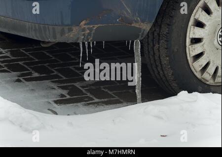 Starker Schneefall beschichtet Pkw und Transporter, wo die Schneeschmelze ist eiskalt mit großen Eiszapfen von der - Stockfoto