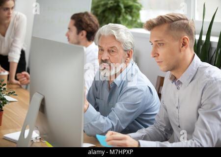 Konzentrierte sich der ältere und junge Kolleginnen und Kollegen diskutieren online Projekt wi - Stockfoto