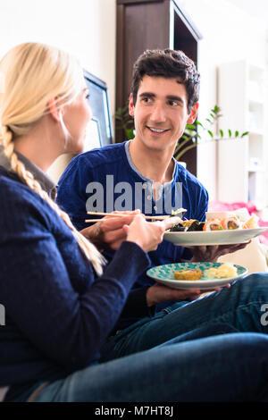 Portrait von glückliches junges Paar Essen traditionelle asiatische Lebensmittel - Stockfoto