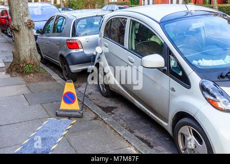 Eine elektrisch angetriebene Auto am Straßenrand in einem Wohnviertel im Norden Londons geladen wird, Großbritannien - Stockfoto