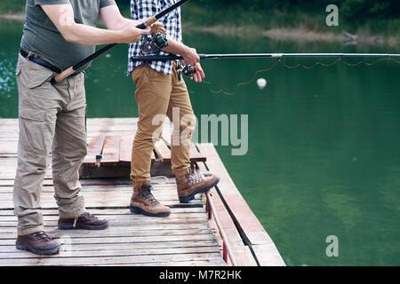 Nicht erkennbare Männer mit Angelrute fischen - Stockfoto