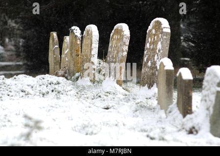 Schnee auf einem Friedhof in einem Dorf, Kirche, Reif, East Sussex. - Stockfoto