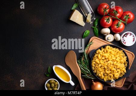 Nudeln und Zutaten zum Kochen auf dunklem Hintergrund, Ansicht von oben. Italienisches Essen Konzept. Pasta, Tomaten, - Stockfoto
