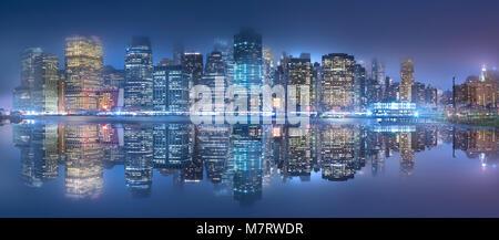 Die New York City Skyline bei Nacht. Über den East River nach Brooklyn Bridge Park fotografiert. - Stockfoto