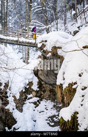 Junge Frauen wandern über Holz- Leitern und Brücken durch verschneite Schlucht Baerenschuetzklamm mit gefrorenen - Stockfoto