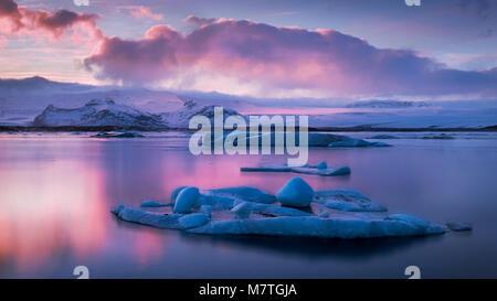 Eisberge auf der Gletscherlagune Jokulsarlon bei Sonnenuntergang im Winter in Island - Stockfoto