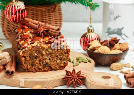 Hausgemachte urlaub Obstkuchen mit Nüssen, Früchten und Gewürzen. Mandeln, Zimt, Sternanis, Kardamom auf dem Tisch. - Stockfoto