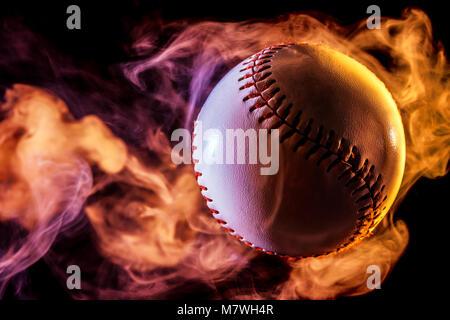 White baseball ball in bunten roten Rauch aus einer isolierten vape auf schwarzem Hintergrund - Stockfoto