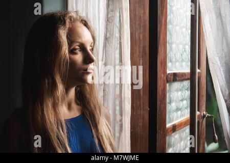 Die Frau in der Nähe eines Fensters - Stockfoto