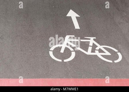 Das Vorzeichen der Radweg auf dem Asphalt und die Richtung der Bewegung. Verkehrszeichen und Fahrbahnmarkierungen. - Stockfoto