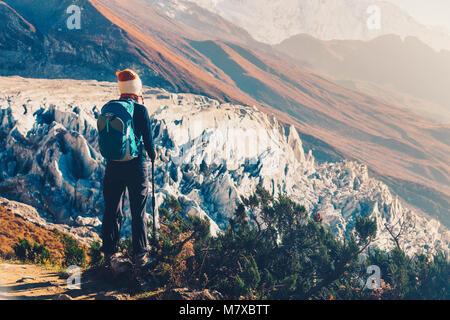 Stehende junge Frau mit Rucksack auf dem Gipfel gegen die schönen Berge und Gletscher bei Sonnenuntergang. Landschaft - Stockfoto