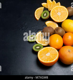Vielzahl von frischen Zitrusfrüchten auf dunklem Hintergrund aus Schichten von Kiwi und Orangen, kopieren Raum Stockfoto