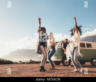 Multi-ethnischen Freunde Tanzen und Spaß haben auf der Rundreise. Gruppe von Menschen, die im Freien genießen. - Stockfoto