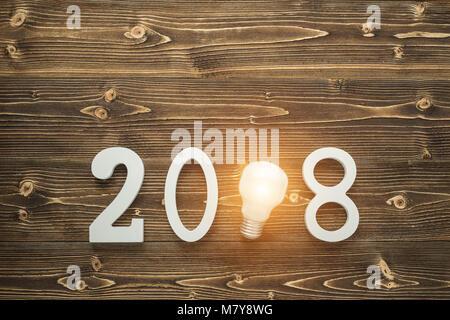Ansicht von oben Glühlampen und weiße Zahl 2018 für das neue Jahr und Urlaub Konzept auf braun Holzbrett. Idee Konzept. - Stockfoto