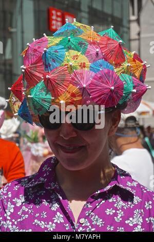 Junge Frau mit Hut mit Cocktail Sonnenschirme an der Fifth Avenue Ostern Parade in New York City. - Stockfoto